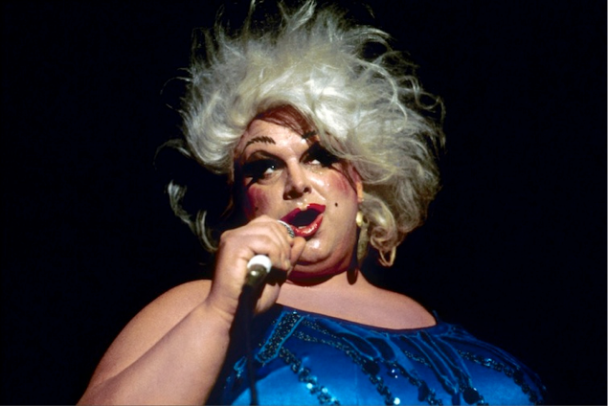 "Animators based the design for Ursula off of the popular Hollywood drag queen Divine, known for being a transvestite (Martin and Kazyak, 320 and Pinksy, 140). Ursula's pronounced masculine physique, with her wide, broad shoulders and muscular frame, seem to disconcertingly map female on to a stereotypically male body - a deceptively female ""illusion"" (McNeal, 354 and Verta et. al, 2123). Drawing on this performative imitation – which Butler argues sustains the system of gender normativity - McNeal explains: ""Because the drag queen is a double mimesis- that is, an imitation of an imitation - s/he is in a perfect position to point out, criticize, and call attention to the fragility and difficulty of performing femininity by heterosexual, anatomical women"" (McNeal, 360). Ursula, as a subversive character who disrupts the traditional expectations of gender, may destabilize the ritualized understandings of performing ""female."" Thus, within the narrative, she is punished for stepping outside of this realm and challenging these norms (Verta et. al, 2123). Ursula is punished multiple times: initially, through ex-communication in Atlantica, and later through her death at the end of the film (Butler, 129). In other words, Ursula's ""bad"" physical appearance and unattractively mapped body are attributed to her ""bad"" personality. As a drag queen with heightened male qualities, Ursula is framed as problematic because of her ""double inversion"" as a figure who is female, yet somehow masculine (Butler, 137). Everything about Ursula is presented as dangerous throughout the course of the narrative; whether it is her black, form-fitting outfit that shows all of her unflattering curves, her husky masculine voice, or her distant, eerie, and abandoned residence, Ursula is a creature who is distinctly and physically deviant to conventional ""woman,"" and she is treated as such. Photo Credit: I Am Divine. Digital image. Jeffrey Schwarz."
